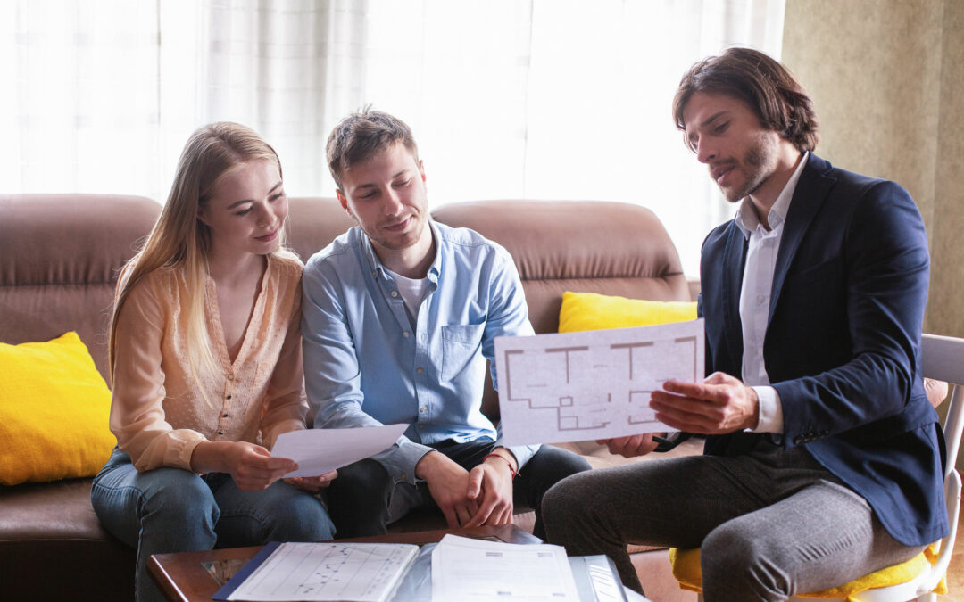 Young couple reviewing plans while house hunting
